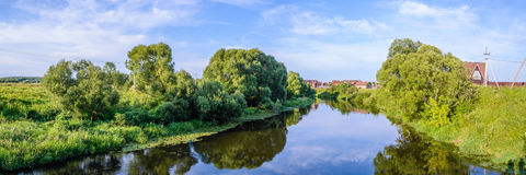 Panorama with river views from the footbridge. Summer warm evening. Panorama with river views from the footbridge. The village is in the background. Reflection Royalty Free Stock Images