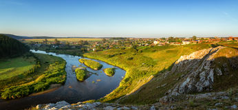 Panorama of the river with a village on the shore in the morning, Russia, Ural Stock Photos
