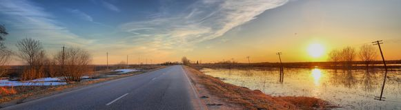 Panorama of the road between the fields with spring flood. Wide-angle view of the sunset over the road between the fields with spring flood royalty free stock photography