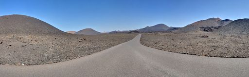Panorama of road in Timanfaya National Park. Panorama of an empty road in Timanfaya National Park. Lanzarote, Canary Islands, Spain, Europe royalty free stock image