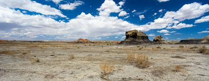 Panorama rock desert landscape in northern New Mexico. In the Bisti/De-Na-Zin Wilderness Area with washed out hoodoo rock formations under a blue sky royalty free stock photography