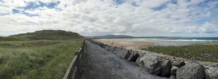 Beach path in Sligo Ireland. Panorama of a rock paved path between tall grass and the beach in Sligo Ireland Royalty Free Stock Image
