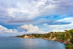Coastline of Jimbaran, South Kuta, Bali, Indonesia. Panorama of the rocky tropical coast, cliffs and stones, green forest and house on the shore, against a Royalty Free Stock Image