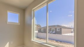 Panorama Room of a new house with a large window overlooking homes mountain and sky. Sunlight beams down on the carpeted floor on this sunny day stock image