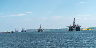 Panorama of a row of decommissioned oil rigs, Cromarty Firth, Sc. Panorama of a row of decommissioned oil rigs from the North Sea in the Cromarty Firth, Scotland Royalty Free Stock Image