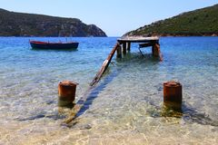 Panorama of a ruined wooden pier and an old fishing boat and mountains in the background of sithonia Greece Royalty Free Stock Images