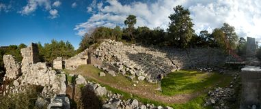 Panorama of the ruins of an ancient amphitheater shot against a blue sky royalty free stock photos