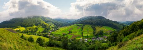 Panorama of a rural area in mountains. Gorgeous forenoon with beautiful clouds on the sky. agricultural fields on hills calm and peaceful life concept royalty free stock images