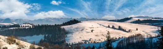 Panorama of rural area in winter Carpathians. Agricultural fields and spruce forests on snowy hillsides. huge mountain ridge in the distance Stock Image