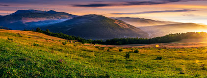 Panorama of rural fields in foggy mountains at sunrise. Panorama of grassy rural fields in foggy mountains at sunrise. beautiful Carpathian countryside landscape Royalty Free Stock Photos