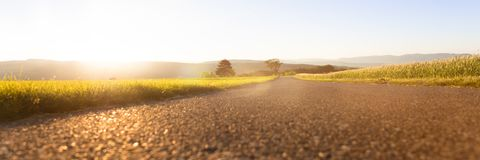 Rural panorama with sunrise. Panorama rural natural scene with a street between meadows at sunrise Royalty Free Stock Photo
