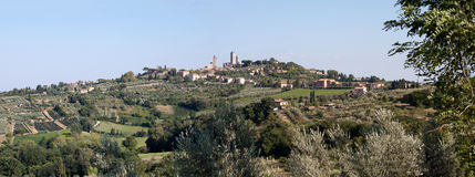 Panorama of San Gimignano. Panorama of the hillside on which sits the ancient Italian town of San Gimignano surrounded by olive groves and vineyards stock photo