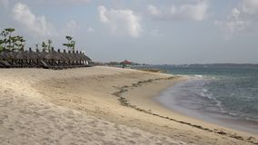 Panorama of the sandy beach with chaise lounges and sunshades in the tropical resort. Bali. Indonesia.  stock footage