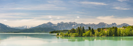 Panorama scene in Bavaria with alps mountains and lake. Panorama scene in Bavaria with mountains mirroring in lake Royalty Free Stock Photography
