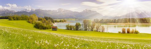 Panorama scene in Bavaria, Germany at alps mountains with sunbeams over lake Royalty Free Stock Photos