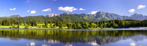 Panorama scene in Bavaria with mountains mirroring in lake Stock Photos