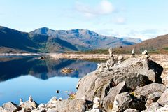 Panorama with Scottish wild mountains valleys and lake with stones royalty free stock images