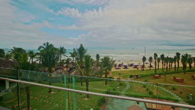 Panorama of Sea Coast with Beach Park from Hotel Terrace. Panorama of sea coast with beach and tropical palm park from hotel terrace against cloudy sky in stock video