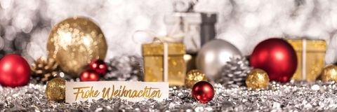 Panorama with shiny christmas decoration and german text. Panorama with shiny gold, red and silver christmas decoration and german text which means merry stock photography