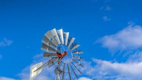 Panorama Shiny steel windpump against a vibrant blue sky with cottony clouds. This multi-bladed windpump is a type of windmill used for pumping water stock photography