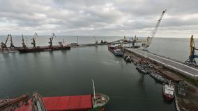 Panorama of ship transporting grain crops at silo terminal in seaport. Cereals bulk transshipment to vessel. Panorama of ship bulk freighter at silo terminal in stock video footage