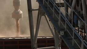 Close panorama of ship loading grain crops on bulk freighter via trunk to open cargo holds at silo terminal in seaport. Panorama of ship loading grain crops on stock video footage