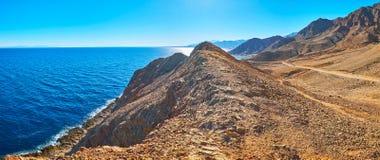 Panorama of Sinai coast, Egypt. The rocky desert coast of Sinai peninsula stretches along the deep blue waters of Aqaba gulf, Egypt royalty free stock photo