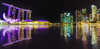 Singapore Skyline by night. Panorama of Singapore buildings and skyscrapers of downtown reflected in the sea. Singapore skyline by night. Night scene waterfront Royalty Free Stock Photos