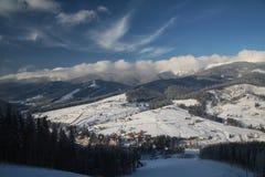 Panorama ski resort in Carpathian mountaines at winter time. Panorama ski resort.Dramatic blue sky.Ski town in the lowlands Royalty Free Stock Photos