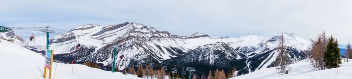 Panorama of Skiers on Chairlift Up a Ski Slope in the Canadian Rockies. Wide angle panorama of skiers and snowboarders on chairlift going up a ski slope in the stock photo