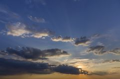 Panorama of sky at sunrise or sunset. Beautiful view of dark blue clouds lit by bright orange yellow sun on clear sky. Beauty and royalty free stock image
