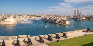 Panorama, skyline of the Maltese capital city Valletta. The Saluting Battery of La Valletta and Fort St. Angelo of La Vittoriosa i. N Malta Royalty Free Stock Photography
