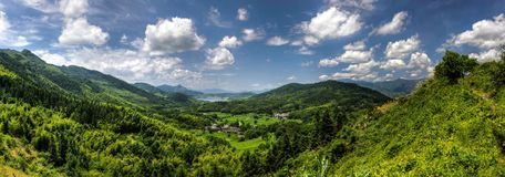 Small village at the bottom of a bright green valley in rural China. Panorama of a small village at the bottom of a bright green valley in rural China royalty free stock images