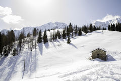 Panorama of snow-covered mountains with hut. Blue sky and clouds Stock Images