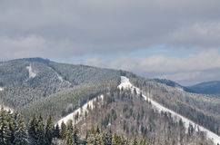 Panorama of snowy mountains and forest in a ski resort. Weather in the mountains. Royalty Free Stock Photography