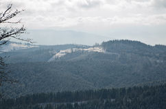 Panorama of snowy mountains and forest in a ski resort. Weather in the mountains. Royalty Free Stock Image