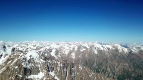 Panorama of snowy peaks, blue sky and brown rocks. Aerial view, horizontal view. A lot of white snow on the mountains stock video