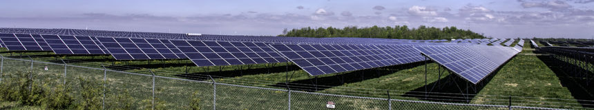 Panorama solar farm. Landscape with solar energy farm nearby Strathroy, Ontario, Canada. In the field are placed thousands of solar panels on frames generating royalty free stock images