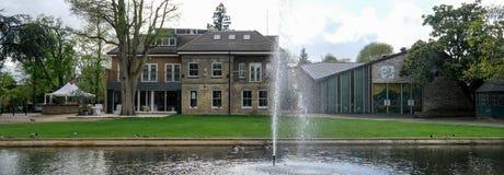 Panorama som tas på en solig vårdag av Pinner Memorial Park, UK, västra hus och Heath Robinson Museum i bakgrunden royaltyfri bild