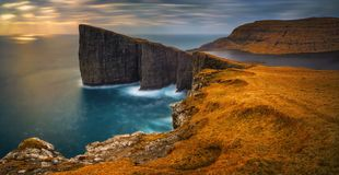 Traelanipa high cliffs. Panorama of Sorvagsvatn lake and cliffs of Traelanipa on Vagar island in sunset, Faroe Islands royalty free stock images