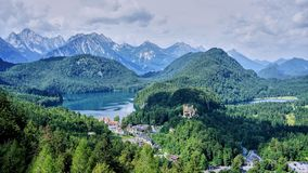 Panorama of Southern Bavaria and the Alps. Wide angle view of the Bavarian countryside including the Hohenschwangau Castle, Alpsee and the mountains of the Alps royalty free stock photography