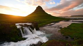 Panorama Spring in western Iceland Kirkyufetl mountain waterfall cascades at sunset.