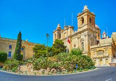 Panorama with St Lawrence Basilica in Birgu, Malta. The scenic tiny garden of Freedom Monument hides the medieval Basilica of St Lawrence with massive bell Stock Photos