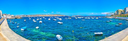 Panorama of St Paul`s Bay marina in Bugibba, Malta. Panorama of St Paul`s Bay marina with moored small fishing boats, and leisure boats on the background stock photos