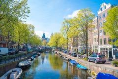 Panorama- stadssikt av Amsterdam med kanaler, broar, cyklar och fartyg Arkivfoto