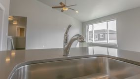 Panorama Stainless steel sink and faucet inside the kitchen of a new house. The room is well lit by the bright sunlight and warm ceiling lights royalty free stock photo