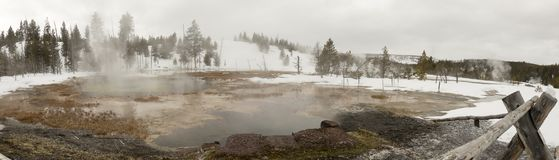 Panorama of steaming hot spring in Upper Geyser Basin, Yellowsto. Panorama of steaming hot spring in snow in Upper Geyser Basin in Yellowstone National Park Stock Image