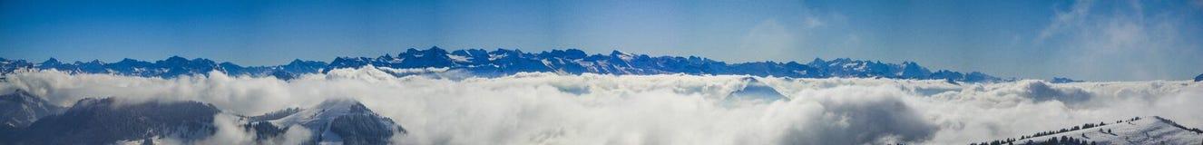 Panorama stupefacente delle alpi svizzere nebbiose e delle nuvole sopra il mounta Fotografie Stock