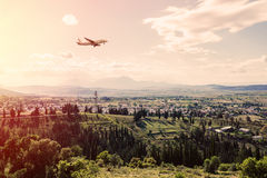 Panorama of the suburbs of the Greek city of Athens with landing plane at sunset Royalty Free Stock Photos