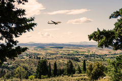 Panorama of the suburbs of the Greek city of Athens with landing plane at sunset Stock Photos